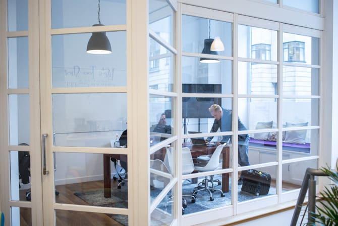 Men Meeting in Glass Office